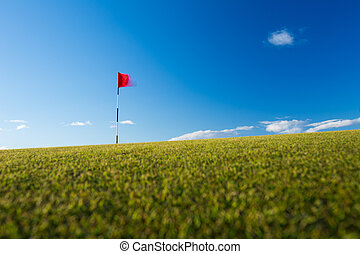 Red golf flag on a golf course, moving in the wind
