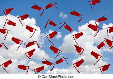 red graduation caps in sky