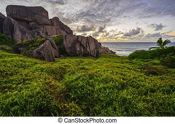 Red granite rocks in the sunrise on la digue on the seychelles 3