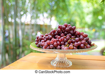 red grape on the step glass plate stand alone on the wood table in the outdoor garden field blur bokeh.