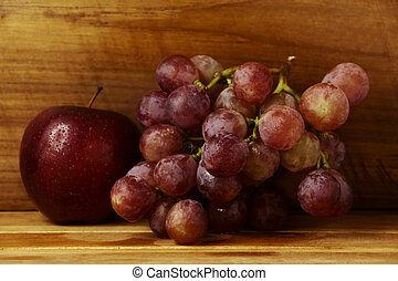 Red grapes and apple on a wooden floor.