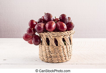 Red grapes in basket on wooden table background