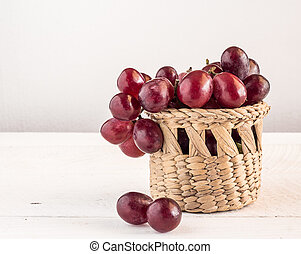 Red grapes in basketl on wooden table background