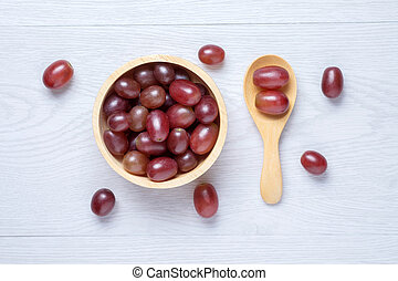 Red grapes in wooden bowl and spoon