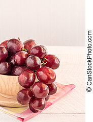 Red grapes in wooden bowl on wooden table background