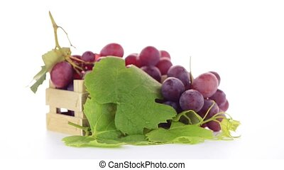 Red grapes in wooden crate isolated on white background.
