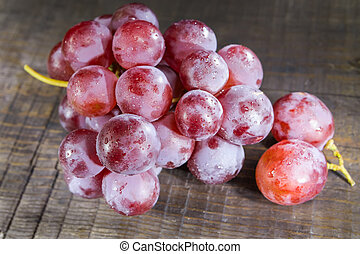 Red grapes on wooden background