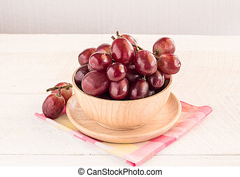 Red grapes on wooden table