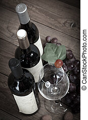 red grapes with wine bottles on brown background