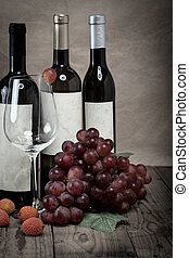 red grapes with wine bottles on wooden background