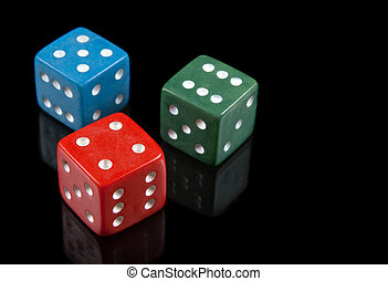 Red, green and blue dices on black background