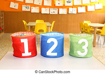 Red Green and blue jars with written one two and three above the table