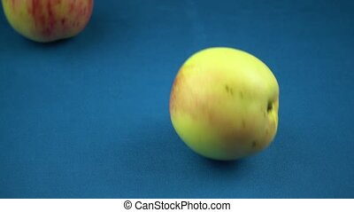 Red-green apples roll on the turquoise surface