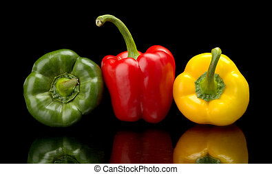 Red, green, yellow bell peppers isolated on black