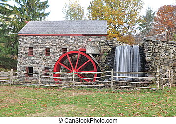 a New England historic grist mill with a red water wheel