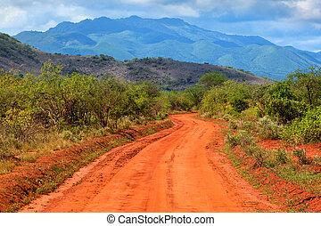 Red ground road and savanna landscape in Africa. Tsavo West, Kenya.