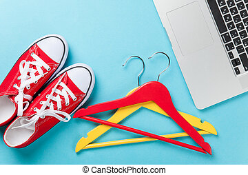 Red gumshoes and hangers near laptop on blue background