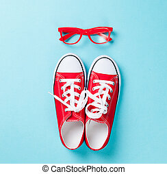 Red gumshoes with white shoelaces and glasses on blue background.