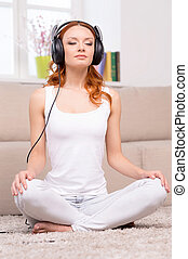 Red hair beauty. Beautiful red hair woman in headphones listening to the music while sitting in lotus position