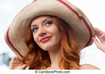 Red hair beauty. Portrait of beautiful young red hair woman in hat smiling and looking away
