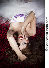 Red Hair. Fashion Girl Portrait. Sensual young lying on red roses blanket