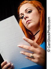 Red hair girl in pin-up style reading a letter