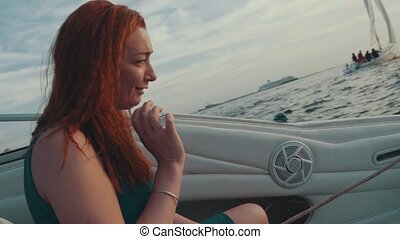 Red hair girl sitting in motor boat holding rope. Summer evening. Entertainment