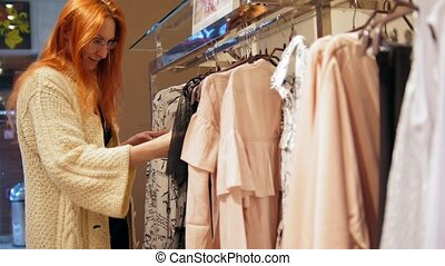 Red hair woman in a clothing store chose a dress - shopping...