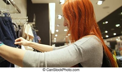 Red hair woman is choosing a dress in women's clothing store...