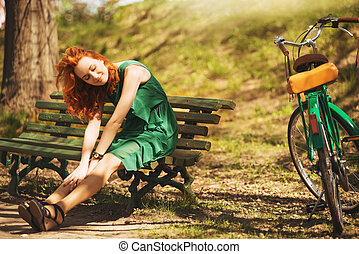 Red-hair woman is seating with retro bicycle