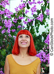 Red hair woman with beautiful flowers of background