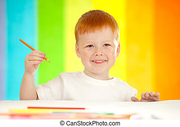 Red-haired adorable boy drawing with orange pencil on rainbow background