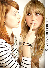 red haired and blond girl sign to shut up with finger