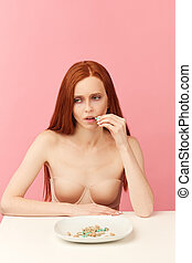 Red-haired anorexic woman in nude underwear eating only slimmimg pill as a diet