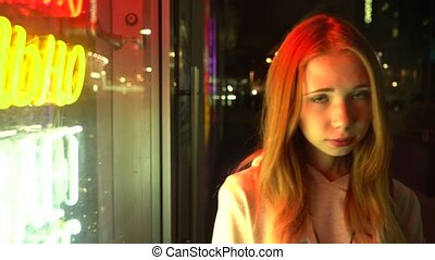 Red-haired beautiful girl alone in a night city