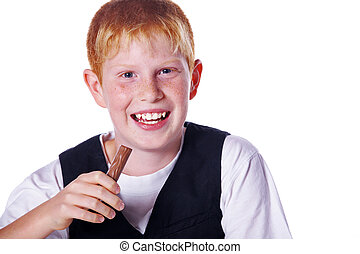red-haired boy eats chocolate bar