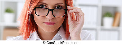 Red haired business woman with glasses who is holding in her...