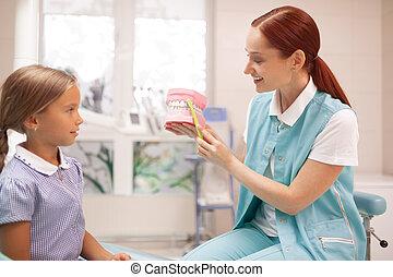 Red-haired child dentist teaching girl to brush teeth properly
