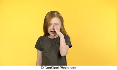 Red-haired child tells secret on yellow background