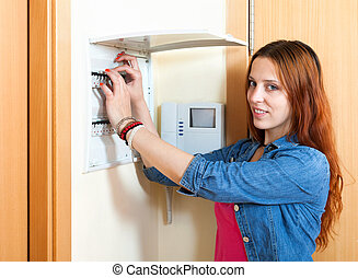 Red-haired cute woman turning off the light-switch at power control panel in home