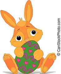 Red-haired easter bunny sitting and holding a painted egg, cartoon on a white background,