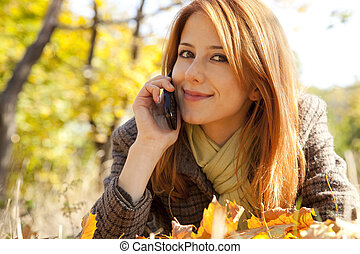 Red-haired girl calling by the phone in the autumn park.