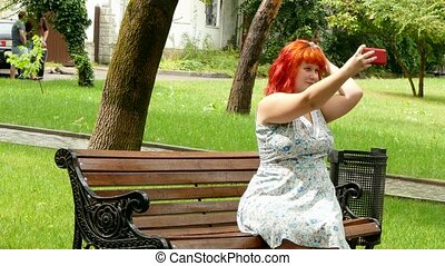 Red-haired girl doing selfie on a park bench - Red-haired...