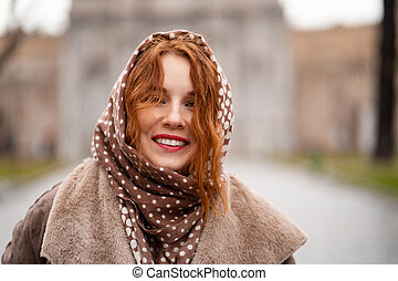 Red-haired girl in a headscarf smiles in the rain