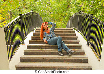 red-haired girl in a warm autumn sweater sitting on the steps of the bridge in the city Park