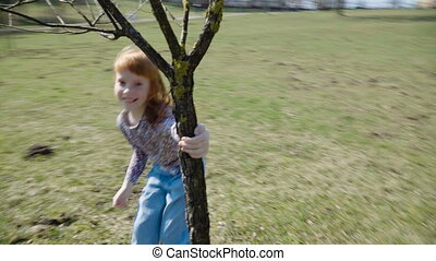 Red-haired girl is playing in a sunny park - Cute ginger...