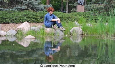 Red-haired girl on the pond - Red-haired girl sitting on the...