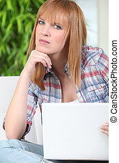red-haired girl sitting on sofa with laptop