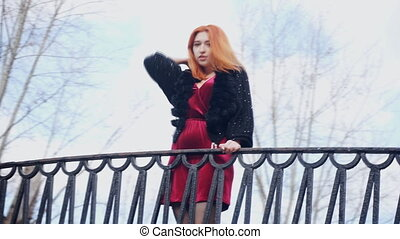 Red-haired girl standing near the railing closeup