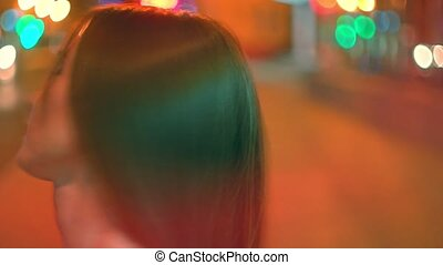 Red haired girl turning about in the street with her long...